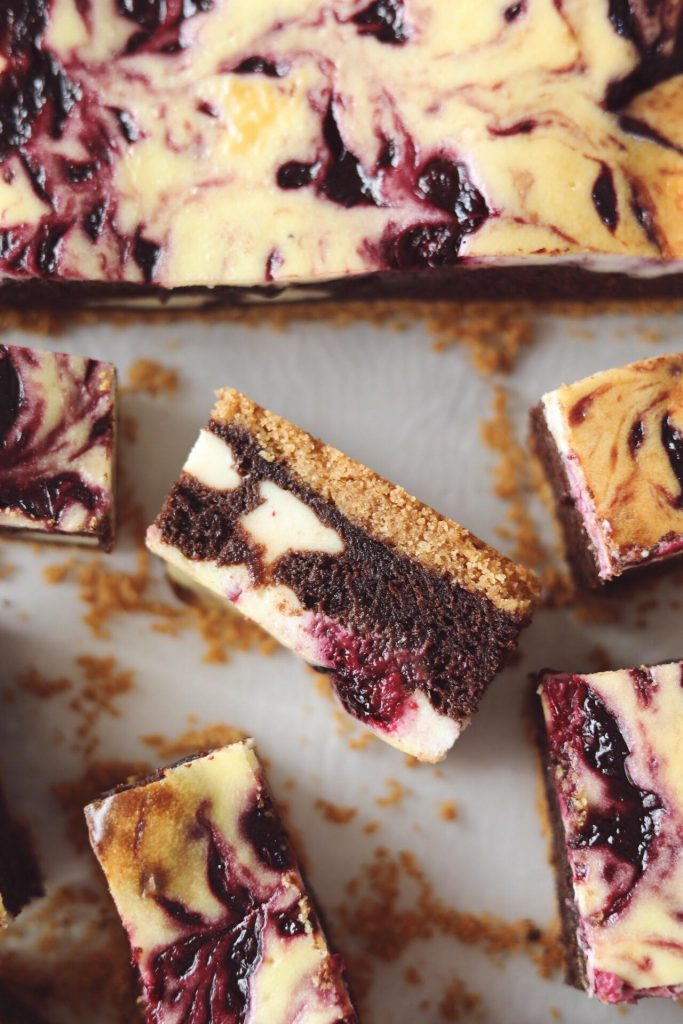 Cheesecake bars med brownie og brombær swirl